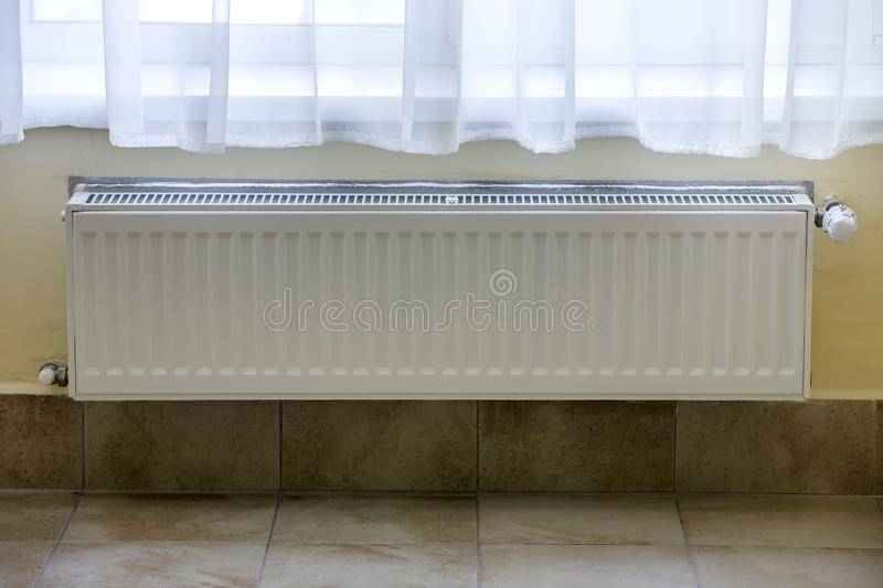 Heating radiator with thermostat valve on light wall tiles copy space background. Comfortable warm home interior, climate control. Money saving concept stock image