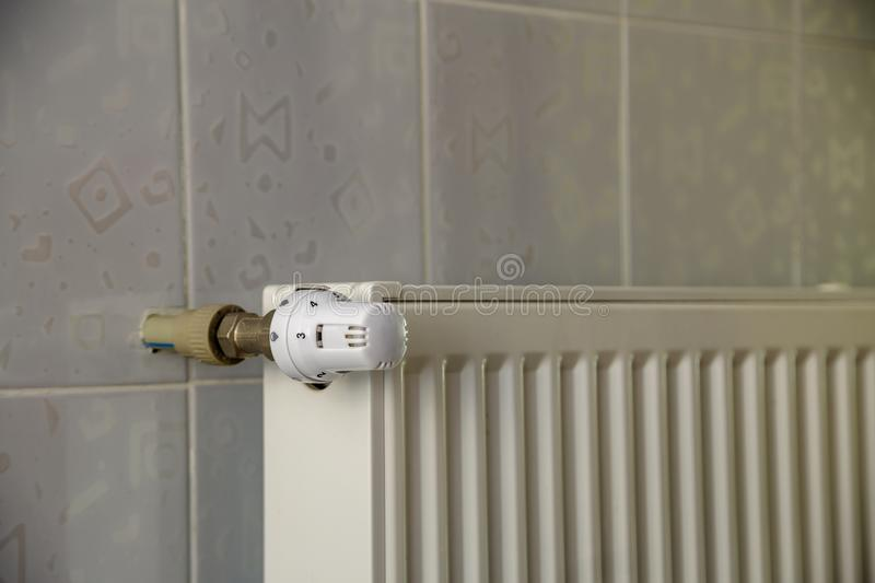 Heating radiator with thermostat valve on light wall tiles copy space background. Comfortable warm home interior, climate control. Money saving concept royalty free stock photos