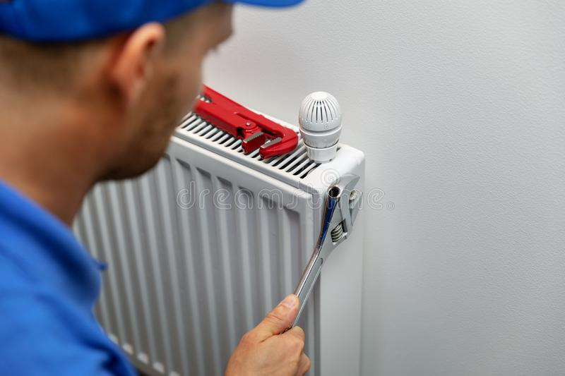 Heating system installation and maintenance service. plumber installing radiator stock photography