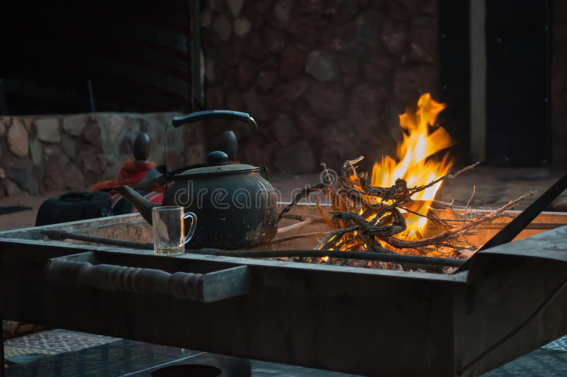 Heating the tea over the fire stock image