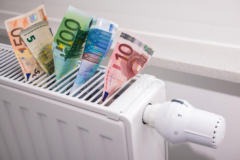 Heating thermostat with money. Expensive heating costs concept royalty free stock photography