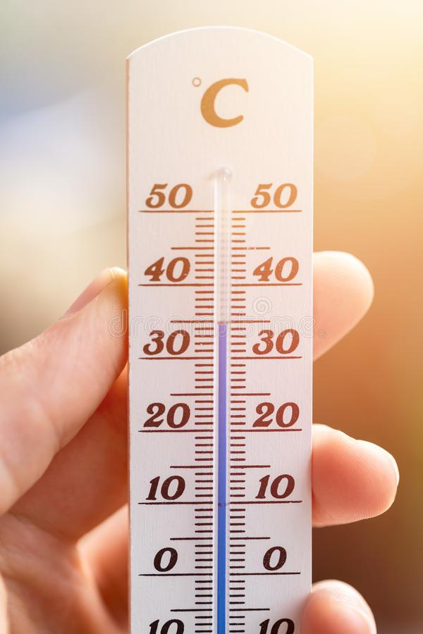 Heatwave: Thermometer in summer on a blurry background, heat. Thermometer close up picture in summer time, blurry background, temperature, heat, wave stock photography