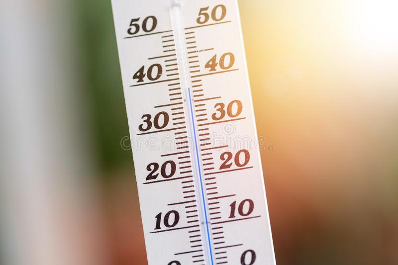 Heatwave: Thermometer in summer on a blurry background, heat royalty free stock images