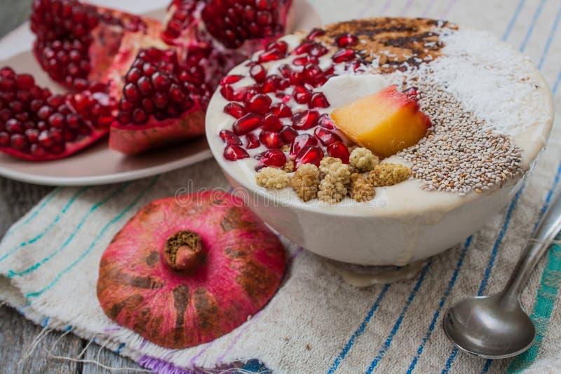 Heavegan banana smoothie with pomegranate, mulberry, coconut, Chia, carob. Raw fruit energy food. stock photo