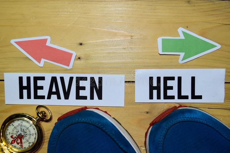 Heaven or Hell opposite direction signs with sneakers and compass on wooden. Vintage background. Business and education concepts stock photo
