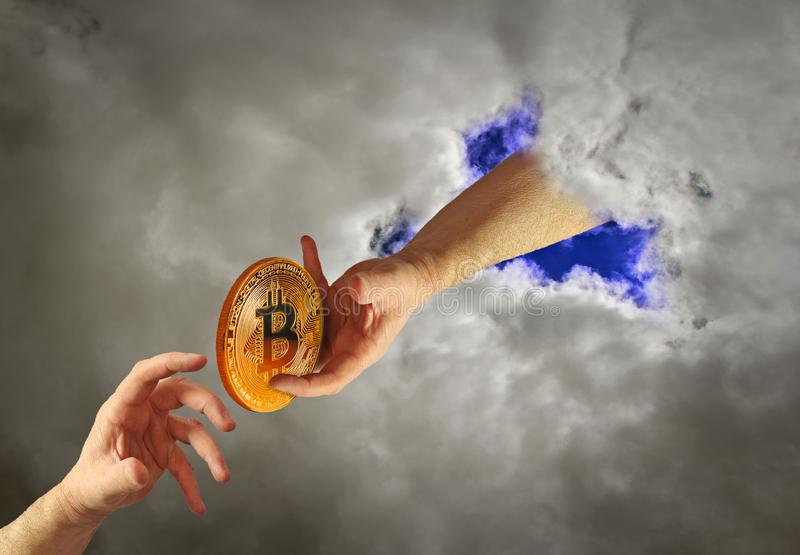 Heavenly bitcoin. Photo of a bitcoin in heavenly hands being given to mortal man concept royalty free stock photo