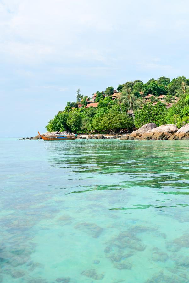 Heavenly green tropical island with clear sea and corals. Heavenly green tropical island with wooden boat, hotel buildings, clear sea and corals under turquoise royalty free stock photos