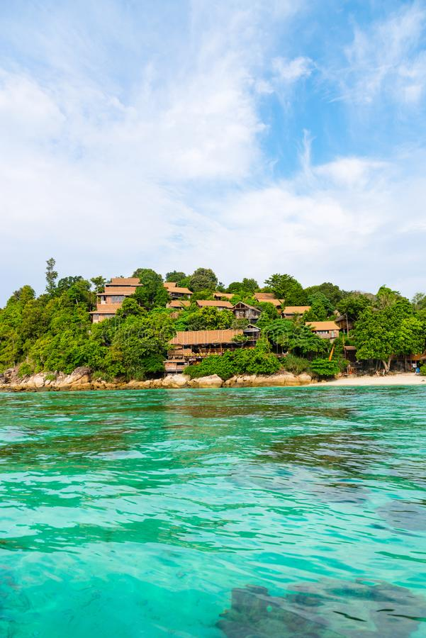 Heavenly green tropical island coast with clear sea and corals. Heavenly green tropical island hill and hotel with clear sea and corals under turquoise water stock photography