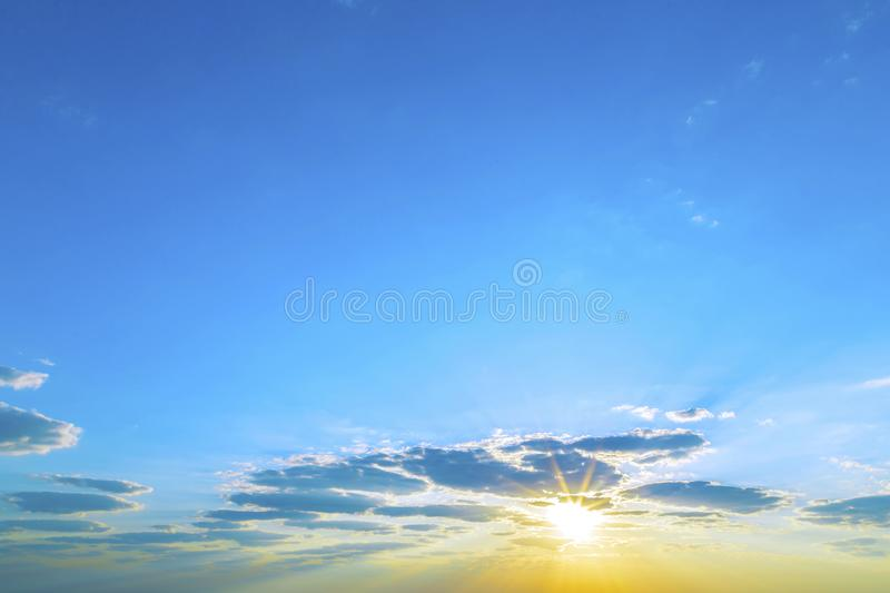 Heavenly landscape, nature. Abstract background. Blue sky with clouds lit by the rays of the yellow sun because of clouds in the stock photography