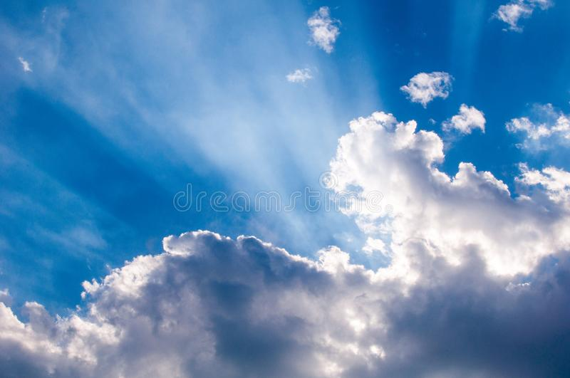 Heavenly sunrays through clouds, wallpaper for desktop. Sky and clouds background royalty free stock photography