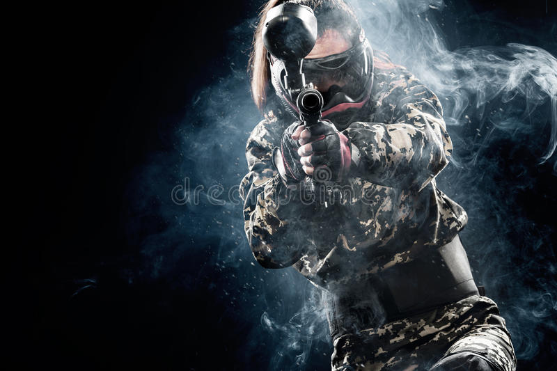Heavily armed masked paintball soldier isolated on black background. Ad concept. royalty free stock image