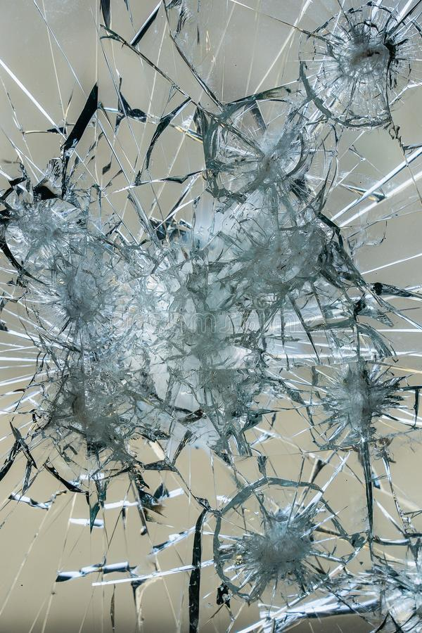 A heavily damaged window pane with large shards and cracks stock photo