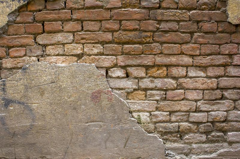 A heavily destroyed old gray concrete wall with red bricks. rough surface texture royalty free stock image