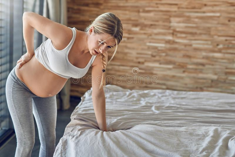 Heavily pregnant young woman suffering with back ache. Leaning on her bed clutching her lower back with an agonised expression royalty free stock photos