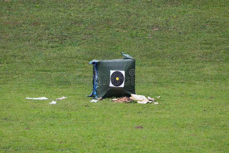 Heavily used archery practice target for bow and arrows mounted on large nylon covered hay bale surrounded with used targets and. Freshly cut grass on warm stock photography