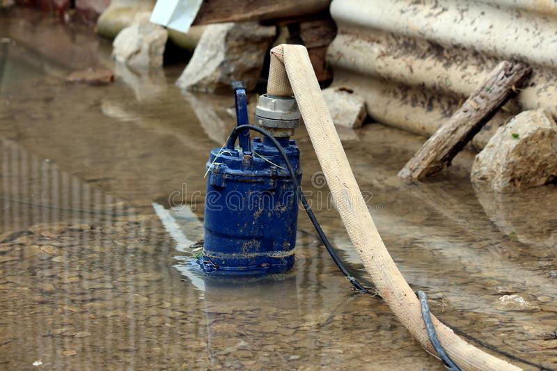 Heavily used old partially submerged metal water pump pumping water from flooded backyard through fire hose surrounded with rocks stock photo