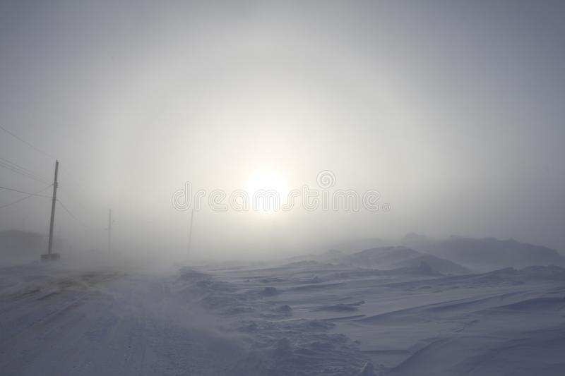 Heavy blowing snow and freezing temperatures along a rural road in the community of Arviat, Nunavut. Canada with a sundog in the background stock photos