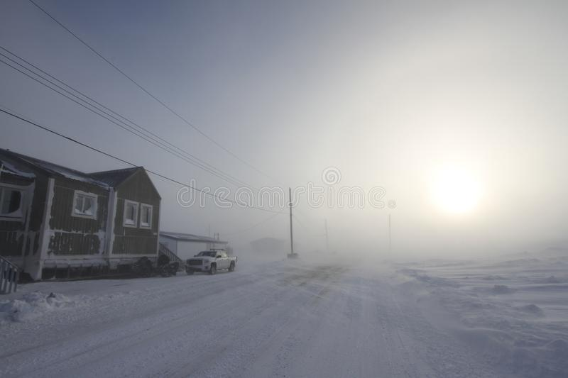 Heavy blowing snow and freezing temperatures along a rural road in the community of Arviat, Nunavut. Canada with a view of an apartment building royalty free stock photography