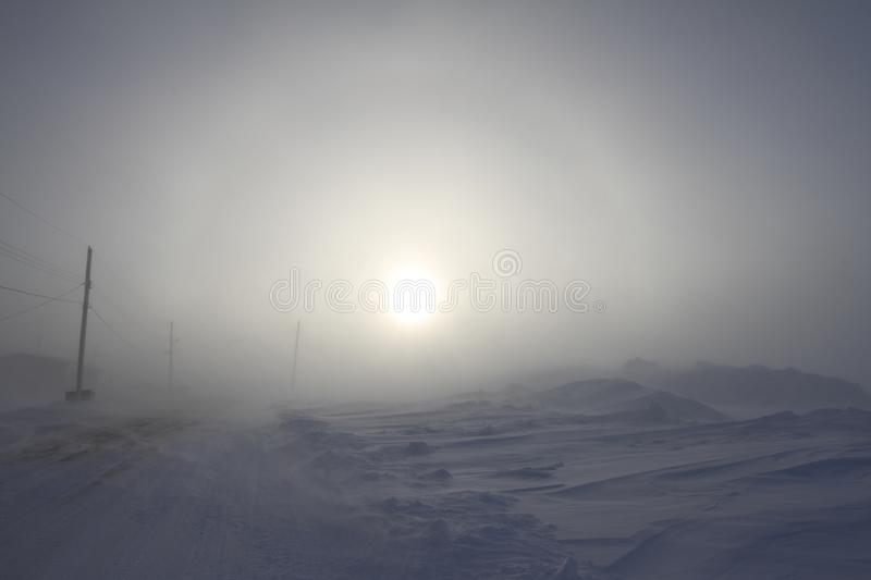 Heavy blowing snow and freezing temperatures along a rural road in the community of Arviat, Nunavut. Canada with a sundog in the background stock images