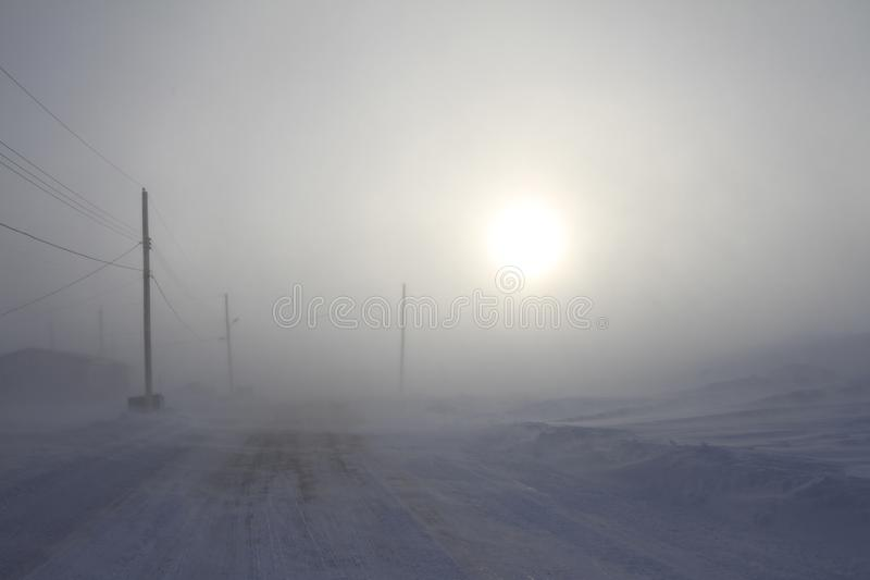 Heavy blowing snow and freezing temperatures along a rural road in the community of Arviat, Nunavut. Canada royalty free stock images