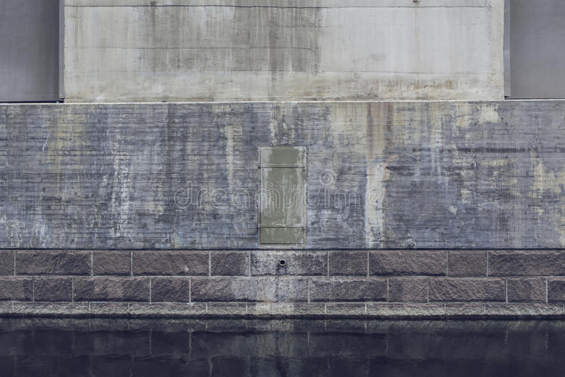Heavy bridge abutment reflecting in water. The base of a heavy stone and concrete bridge abutment reflecting in water royalty free stock photo