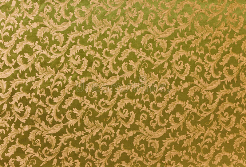 Heavy Brocade Fabric Background. Abstract background of a heavy golden brocade fabric with interwoven repeat design royalty free stock images