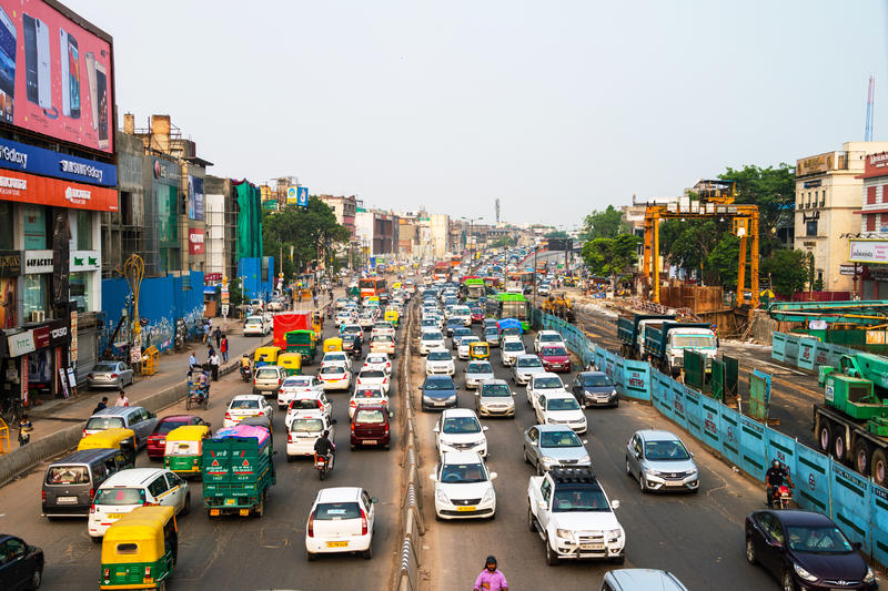 Heavy car traffic in the city center of Delhi, India. DELHI, INDIA - JULY 5, 2016: Heavy car traffic in the city center of Delhi, India. Buses and construction stock photos
