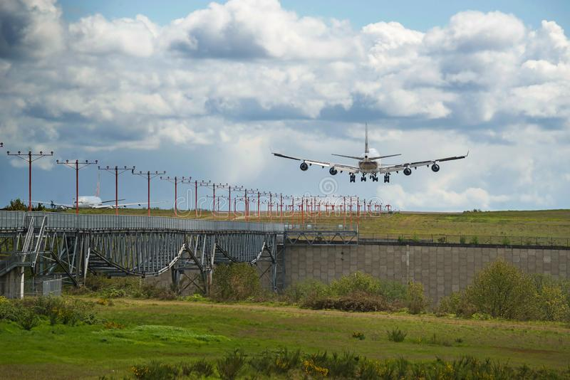 Heavy cargo airplane landing on runway with lush green and blue sky stock images
