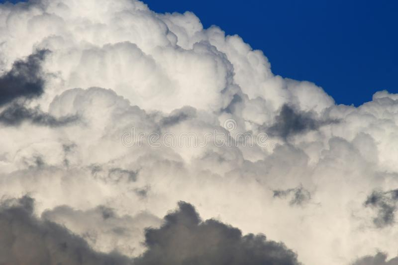 Heavy chubby clouds on blue sky stock photography