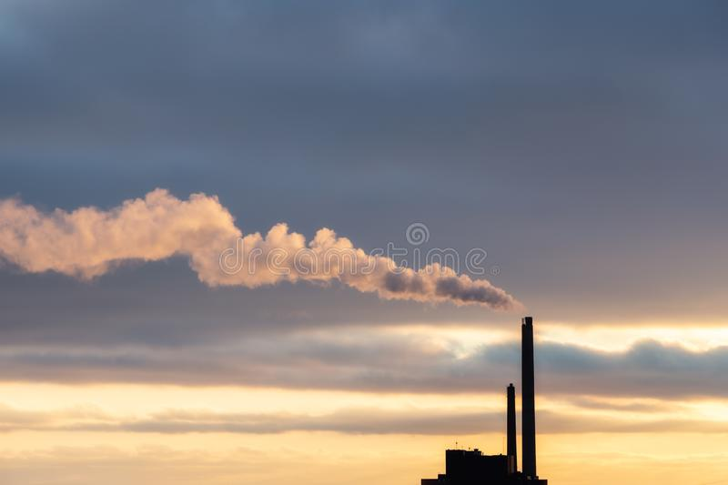 Heavy cloud of smoke from industrial chimney in sunset with copy space royalty free stock image