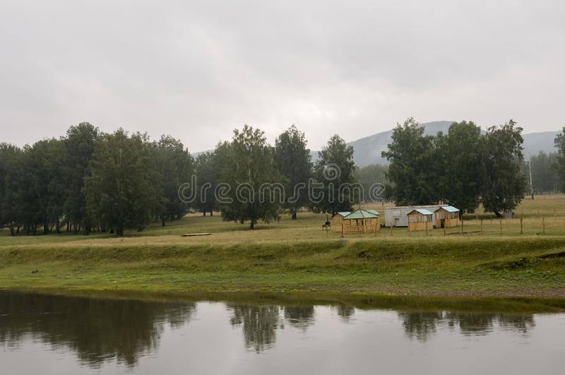 Heavy clouds in the cold autumn sky over  village with small light wooden houses far away in the mountains. Wide river flows near royalty free stock photos