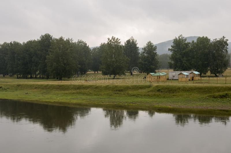 Heavy clouds in the cold autumn sky over  village with small light wooden houses far away in the mountains. Wide river flows near stock photography