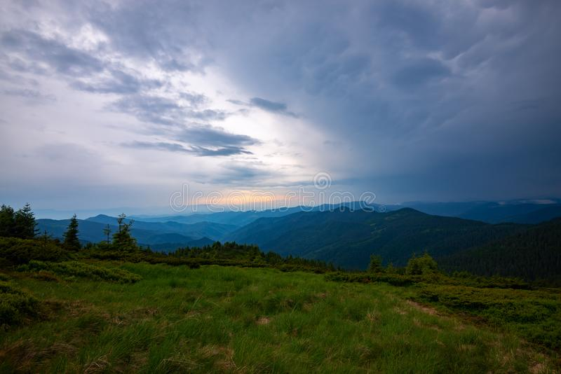 Heavy clouds float above the green hills. Awesome mountain landscape before the storm - heavy gray clouds float above the green wooded hills to the horizon royalty free stock photos