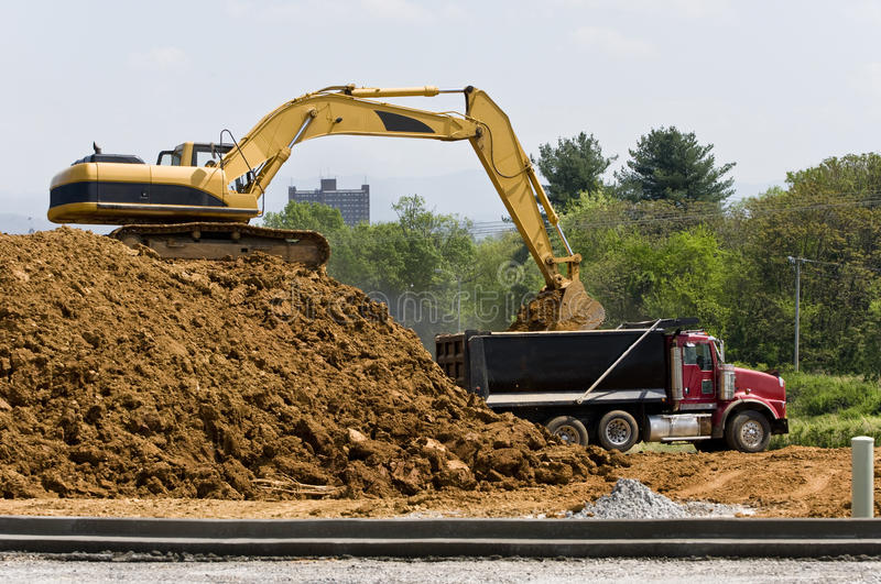 Heavy Construction Equipment With Dump Truck. Heavy construction equipment on top of a pile of dirt and a dump truck royalty free stock images