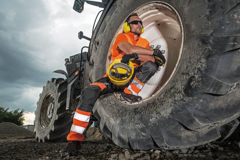 Heavy Construction Equipment. Operating Heavy Construction Equipment. Caucasian Worker Wearing Noise Reduction Headphones and Sunglasses Taking Short Break and stock photos