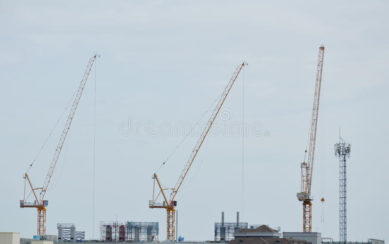 Heavy crane on roof top of under construction building stock image