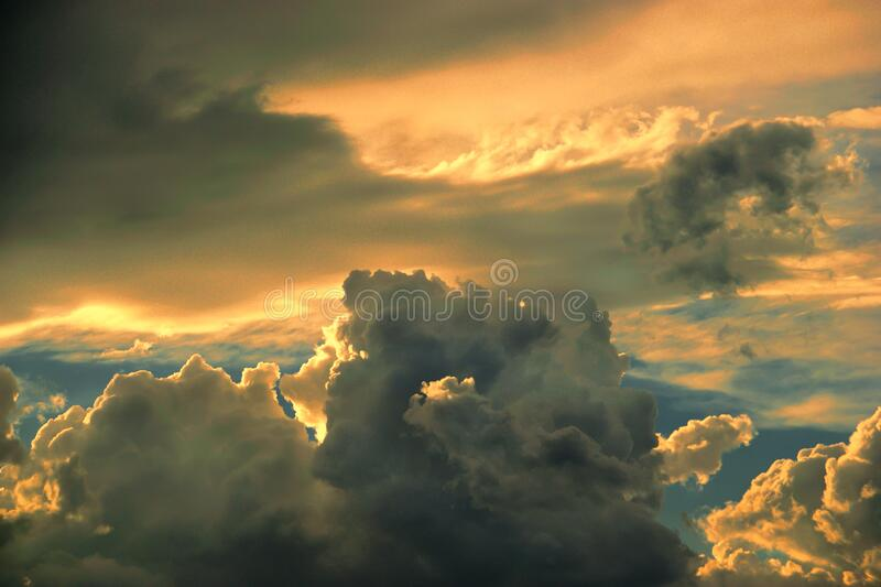 Heavy and dramatic storm cloud formations in colorful summer sky at sunset. Seen from ground level. Copy space stock image
