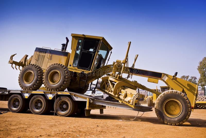 Heavy Duty Hauling Services. Heavy Duty Construction Equipment. Caterpillar 140H grader delivered to construction site, by means of heavy duty logistics services stock photos