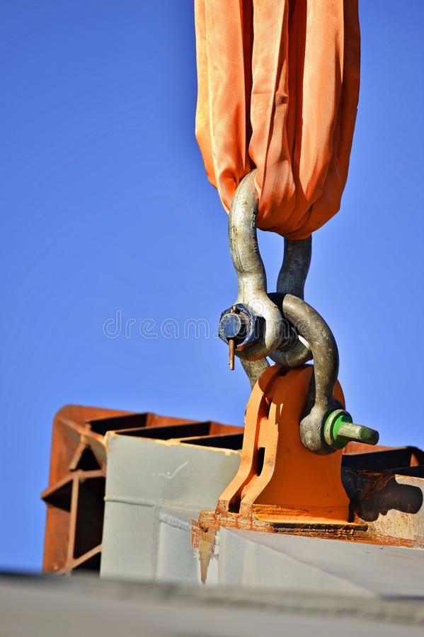 Heavy duty industrial chain lifting concrete structure. Heavy duty chain hooked up on a construction crane lifting concrete a structure royalty free stock images