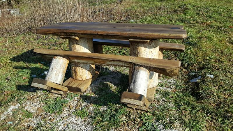Heavy duty strong wooden outdoor table with two benches stock image