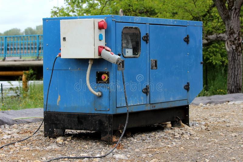 Heavy enclosed industrial power generator located next to river providing electrical power to water pumps pumping flood water away. Heavy enclosed industrial royalty free stock photos
