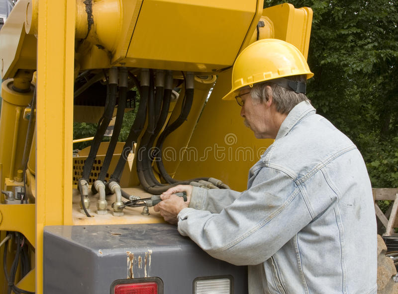 Heavy equipment mechanic. Repairing hydraulic hoses stock photos