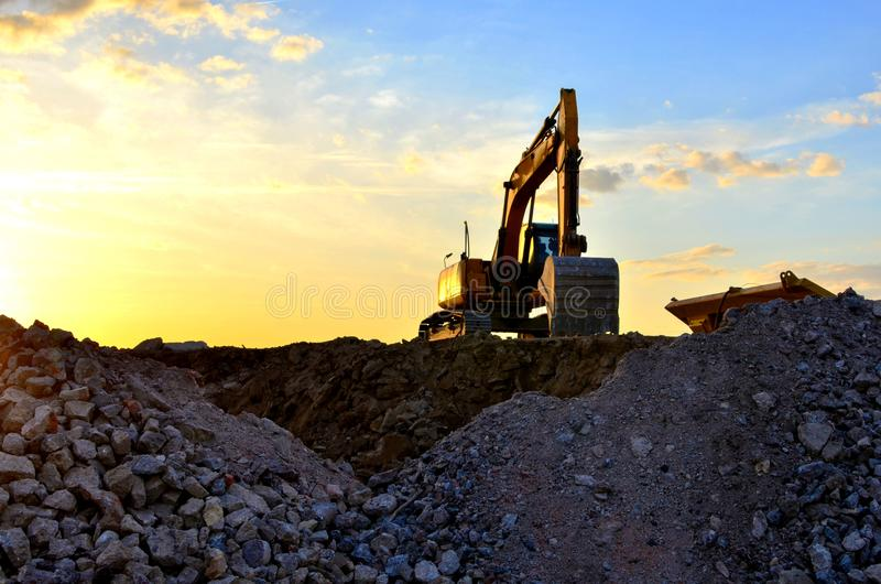Heavy excavator bucket working in quarry on a background of sunset and blue sky. Mobile jaw stone crusher by the construction site stock photos