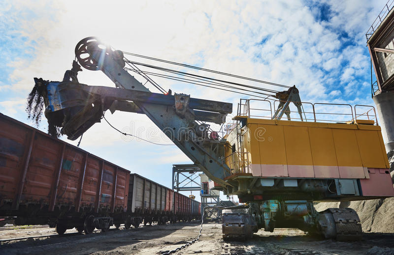Heavy excavator loading gravel into train for rail freightage stock photos