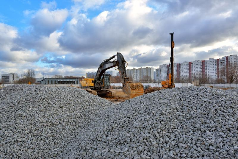 Heavy excavator and pile driving machine on a construction site. A pile of gravel in the foreground royalty free stock photo