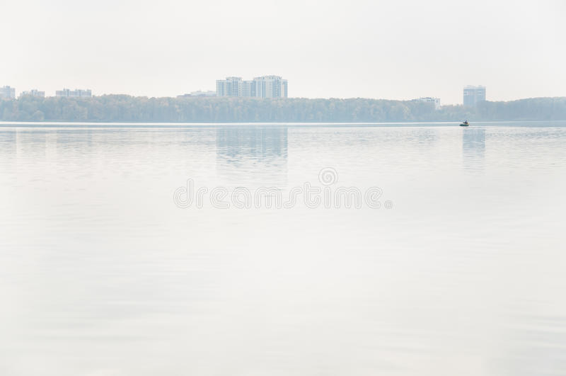 Heavy fog on the lake Senezh in Solnechnogorsk fall in calm weather. View of the residential high-rise buildings through the haze. Autumn morning water stock images