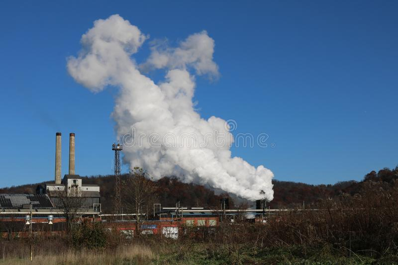 Heavy Industrial Coke Battery Quench Landscape. Coke Battery Quench Steam and Heavy Industrial Double Stacks at Coke Battery in Front of Rolling Hilly Mountain royalty free stock image