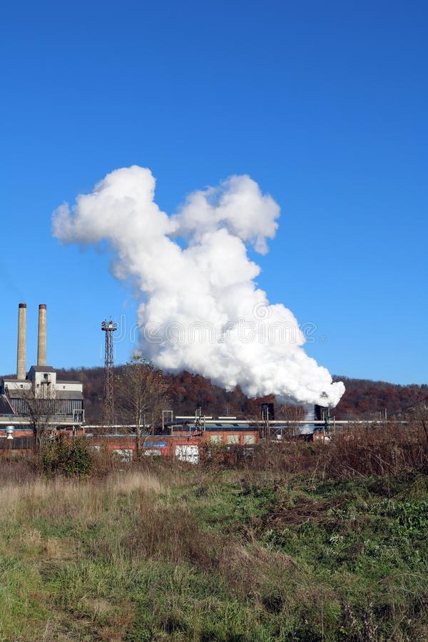 Heavy Industrial Coke Battery Quench Portrait. Coke Battery Quench Steam and Heavy Industrial Double Stacks at Coke Battery in Front of Rolling Hilly Mountain stock photography