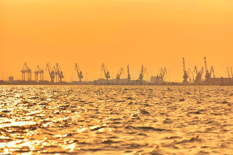 Heavy industrial port equipment, big cranes in sunset light.  stock photos