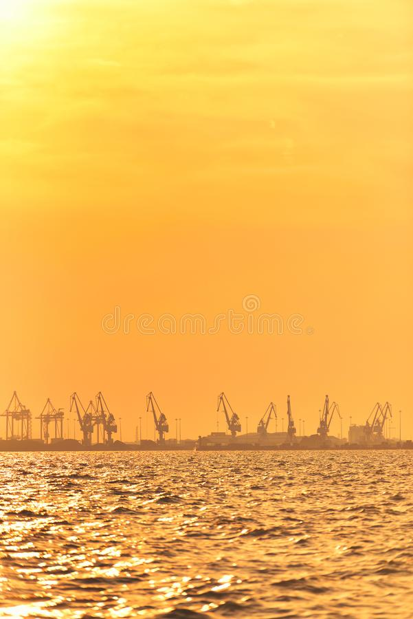 Heavy industrial port equipment, big cranes in sunset light.  royalty free stock image